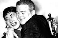 """<p>Best Supporting Actor and Actress winners Red Buttons and Miyoshi Umeki hugged it out after nabbing Oscars for their roles in <em>Sayonara</em>. The ceremony had multiple hosts including Bob Hope, Rosalind Russell, David Niven, James Stewart, Jack Lemmon, and ... Donald Duck<span class=""""redactor-invisible-space"""">.</span></p>"""