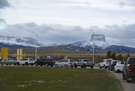 In this Thursday, April 29, 2021, photo, Canadians drive-in at the Piegan-Carway border to receive a COVID-19 from the Blackfeet tribe near Babb, Mont. The Chief Mountain, sacred to the Blackfeet tribe towers, are seen in the background. The Blackfeet tribe gave out surplus vaccines to its First Nations relatives and others from across the border. (AP Photo/Iris Samuels)