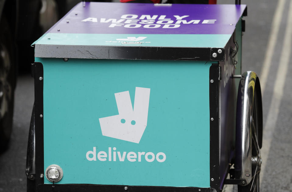 FILE - In this Tuesday, July 11, 2017 file photo, a deliveroo logo is seen on a bicycle in London. A British food delivery company has decided to pay an undisclosed amount to settle legal claims by fifty of its riders. Many said they were paid below minimum wage and denied holiday pay. The settlement was announced Friday, June 29, 2018 by the riders' law firm, Leigh Day, and is the latest victory in a string of worker claims against gig economy employers. (AP Photo/Frank Augstein, file)