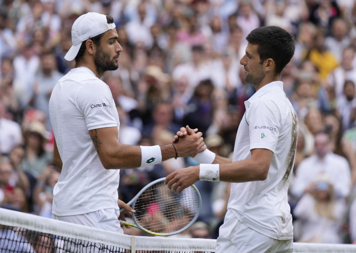 Serbia's Novak Djokovic, right, shakes hands with Italy's Matteo Berrettini after defeating him in the men's singles final on day thirteen of the Wimbledon Tennis Championships in London, Sunday, July 11, 2021. (AP Photo/Kirsty Wigglesworth)