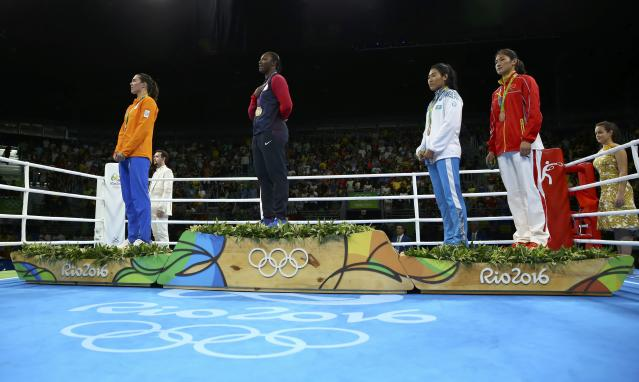 2016 Rio Olympics - Boxing - Victory Ceremony - Women's Middle (75kg) Victory Ceremony - Riocentro - Pavilion 6 - Rio de Janeiro, Brazil - 21/08/2016. (From L) Silver medallist Nouchka Fontijn (NED) of Netherlands, gold medallist Claressa Shields (USA) of USA and bronze medallists Dariga Shakimova (KAZ) of Kazakhstan and Li Qian (CHN) of China stand during the singing of the national anthem. REUTERS/Peter Cziborra FOR EDITORIAL USE ONLY. NOT FOR SALE FOR MARKETING OR ADVERTISING CAMPAIGNS.