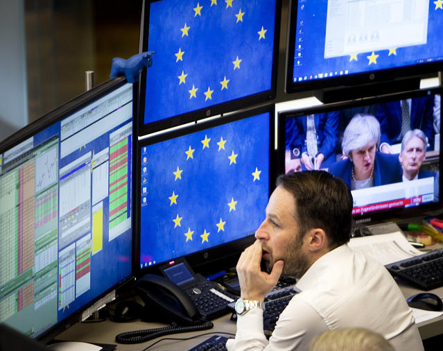 A computer screen shows news about Brexit with British Prime Minister Theresa May as a broker watches his screens at the stock market in Frankfurt, Germany, Wednesday, Jan. 16, 2019. (AP Photo/Michael Probst)