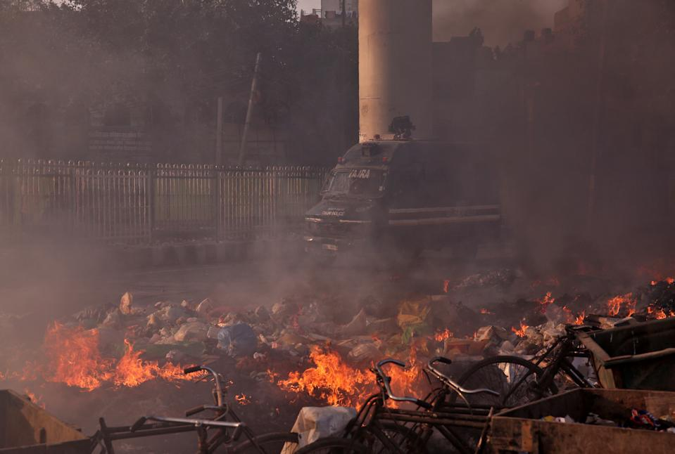 A police vehicle moves past burning debris that was set on fire by demonstrators in a riot affected area after fresh clashes erupted between people demonstrating for and against a new citizenship law in New Delhi, India, February 25, 2020. REUTERS/Danish Siddiqui