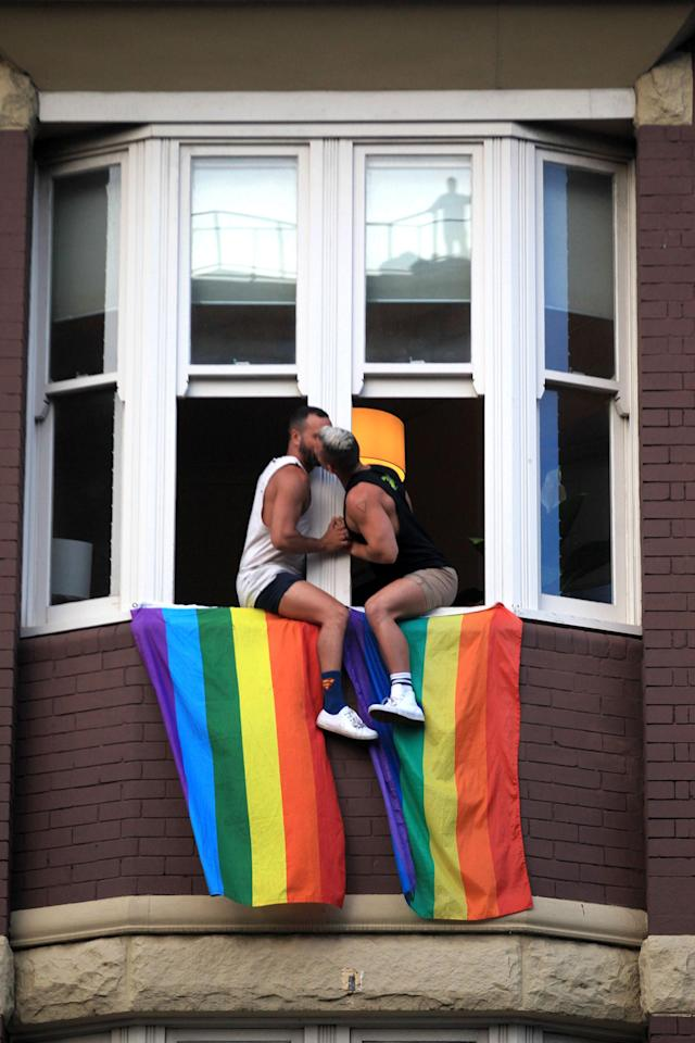 <p>A couple kiss as they sit at their window as crowds supporting the Same Sex Marriage Survey march down Oxford St., and into the city whilst a same sex couple embrace above in a window on Nov. 15, 2017 in Sydney, Australia. (Photo: James Alcock/Getty Images) </p>