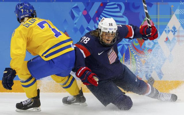 Team USA's Kacey Bellamy is checked by Sweden's Johanna Olofsson during the first period of their women's ice hockey semi-final game at the Sochi 2014 Winter Olympic Games