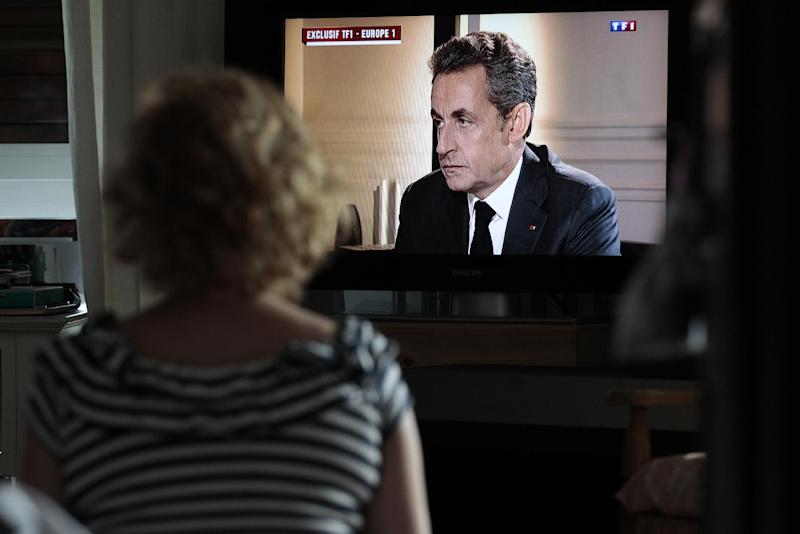 A woman watches a televised interview with former French president Nicolas Sarkozy, after he was charged with corruption and influence peddling, in Caen, northwestern France, on July 2, 2014 (AFP Photo/Charly Triballeau)