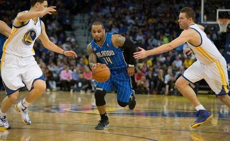 Orlando Magic guard Jameer Nelson (14) drives in between Golden State Warriors guard Klay Thompson (11) and forward David Lee (10) during the second quarter at Oracle Arena. Mar 18, 2014; Oakland, CA, USA; Kelley L Cox-USA TODAY Sports -