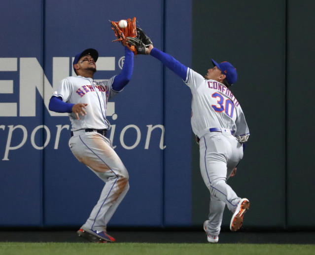 New York Mets center fielder Juan Lagares, left, nearly collides with right fielder Michael Conforto while catching a fly ball by St. Louis Cardinals' Marcell Ozuna to end the third inning of a baseball game Friday, April 19, 2019, in St. Louis. (AP Photo/Jeff Roberson)