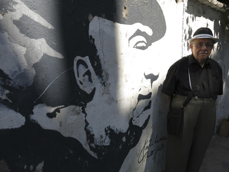 Hernan Loyola, a friend of Chilean Nobel laureate Pablo Neruda, poses for a photo in front of a mural of Neruda painted on a wall near the poet's home in, Santiago, Chile, Friday, Nov. 8, 2013. Loyola, who is considered one of the world's top experts in Neruda literature, has also written several books about the poet. The four-decade mystery of whether Neruda was poisoned was seemingly cleared up on Friday, when forensic test results showed no chemical agents in his bones. But his family and driver were not satisfied and said they'll request more proof. (AP photo/Luis Andres Henao)