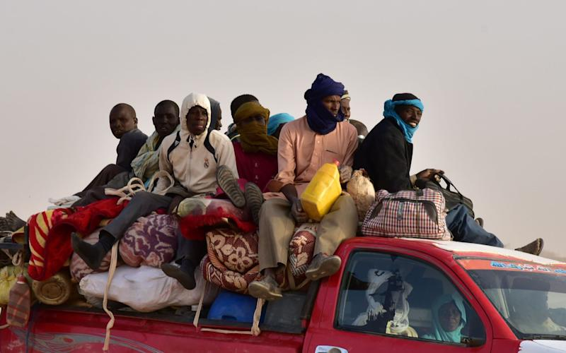 West African migrants on a pick-up truck near the Libya-Niger border, in the Sahara Desert - AFP