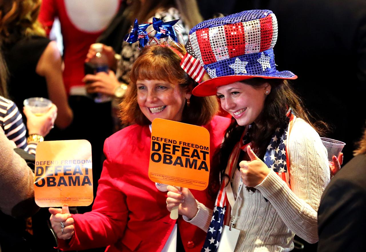 "BOSTON, MA - NOVEMBER 06: People hold up signs saying, ""Defend Freedom, Deafeat Obama"", while wearing patriotic hats during Mitt Romney's campaign election night event at the Boston Convention & Exhibition Center on November 6, 2012 in Boston, Massachusetts. Voters went to polls in the heavily contested presidential race between incumbent U.S. President Barack Obama and Republican challenger Mitt Romney.  (Photo by Joe Raedle/Getty Images)"