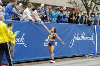 American Nell Rojas is congratulated after crossing the finish line of the 125th Boston Marathon on Monday, Oct. 11, 2021, in Boston. (AP Photo/Winslow Townson)