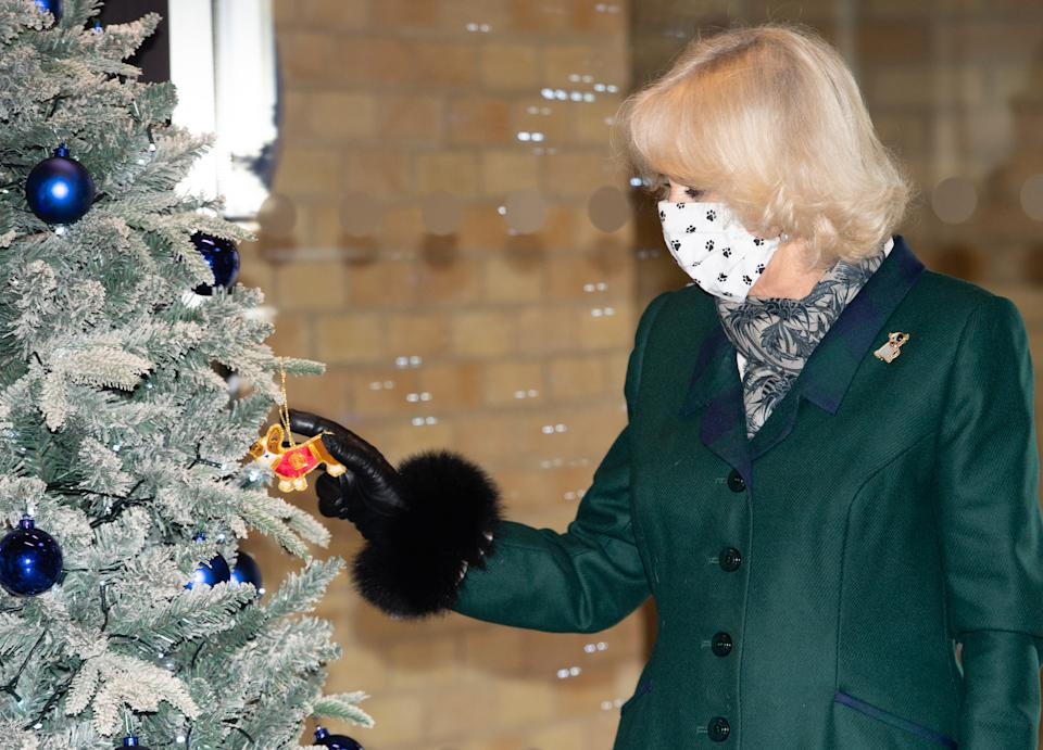 WINDSOR, ENGLAND - DECEMBER 09: Camilla, Duchess of Cornwall decorates a Christmas tree as she visits Battersea Dogs Home in Windsor on December 09, 2020 in Windsor, United Kingdom. (Photo by Samir Hussein/WireImage)