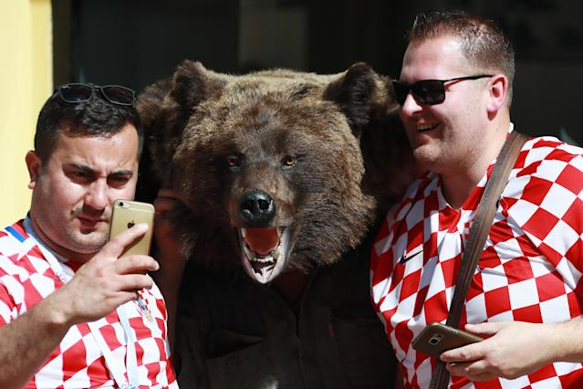 <p>Croatian football fans pose for a picture with a bear figure in a street during the 2018 FIFA World Cup. Vladimir Smirnov/TASS (Photo by Vladimir Smirnov\TASS via Getty Images) </p>
