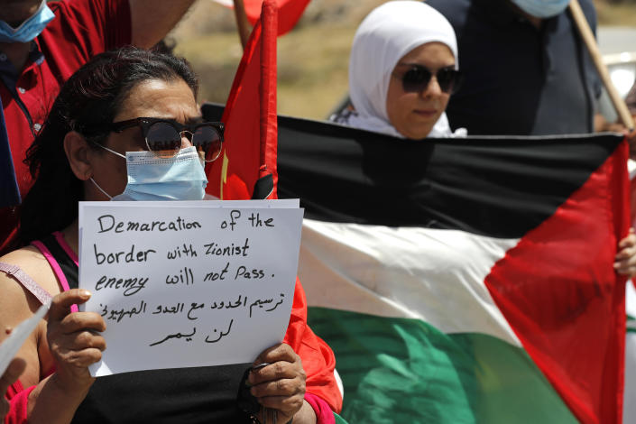 Lebanese protesters hold a placard and the Palestinian flag, during a sit-in on a road that leads to a U.N. post along the Lebanon-Israel border known as Ras Naqoura where Lebanese and Israeli delegations are meeting, in Naqoura, Lebanon, Tuesday, May 4, 2021. After a nearly six-month pause, Lebanon and Israel on Tuesday resumed indirect talks with U.S. mediation over their disputed maritime border. (AP Photo/Hussein Malla)