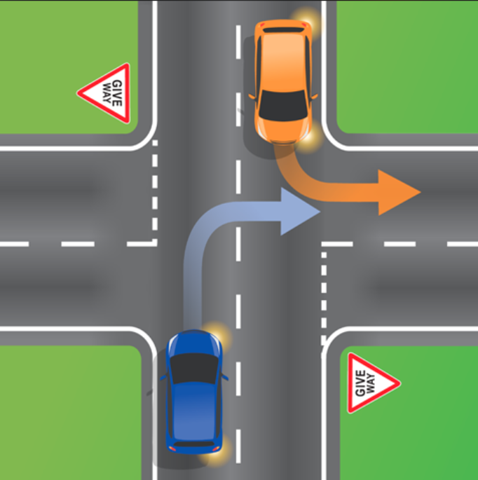 Pictured is an orange car indicating to turn left into a street while a blue car in the opposite direction indicates to turn right down the same street.