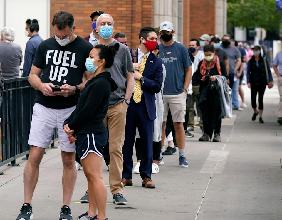 Voters line up and wit to cast a ballot at the American Airlines Center during early voting Thursday, Oct. 15, 2020, in Dallas. (AP Photo/LM Otero) ORG XMIT: TXMO102