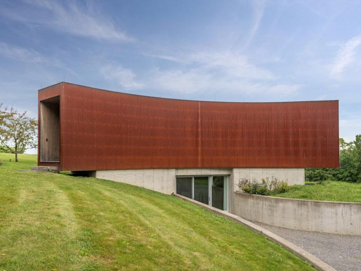 The guest house of the Tsai Residence is clad in a rusted Corten steel, and comes complete with a sunken walkway.