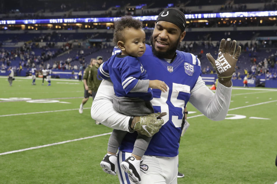 FILE - In this Nov. 11, 2018, file photo, Indianapolis Colts tight end Eric Ebron (85) carries his son as he leaves the field following an NFL football game against the Jacksonville Jaguars in Indianapolis. Ebron is embracing a fresh start in Pittsburgh after an ugly divorce with the Indianappolis Colts. The Steelers signed Ebron to a two-year contract last week. (AP Photo/Darron Cummings, File)