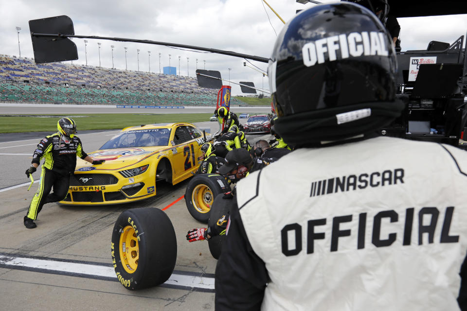 A race official looks on as Matt DiBenedetto makes a stop on pit road during a NASCAR Cup Series auto race at Kansas Speedway in Kansas City, Kan., Sunday, May 2, 2021. (AP Photo/Colin E. Braley)