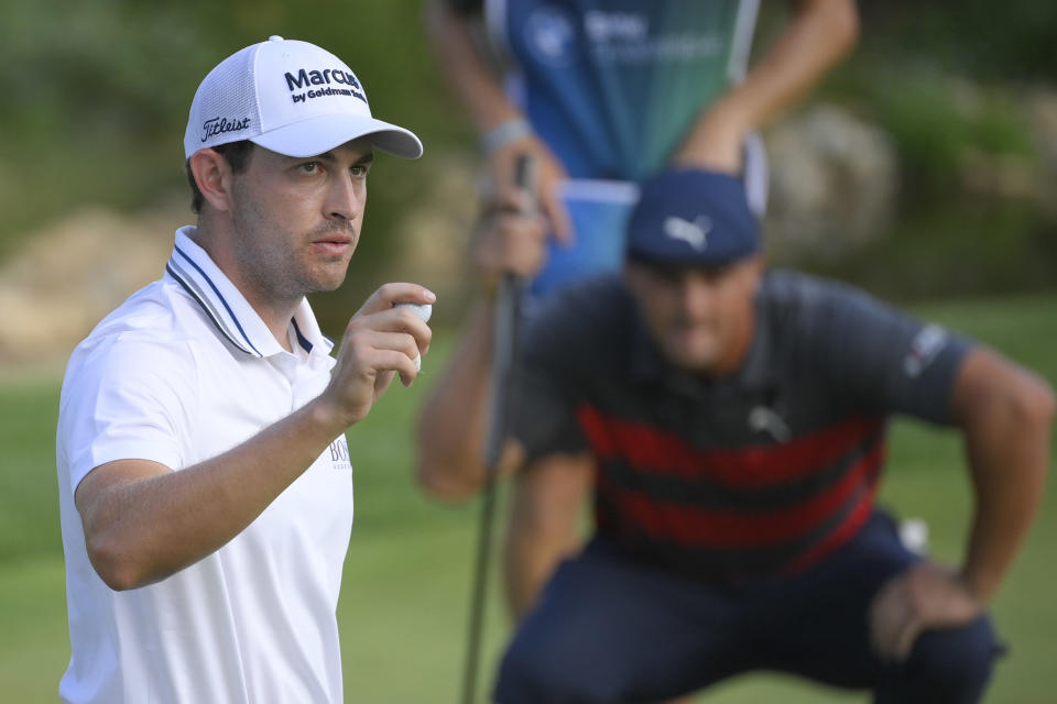 Patrick Cantlay, left, reacts after sinking his putt on the 18th green as Bryson DeChambeau, right, lines up his putt during the final round of the BMW Championship golf tournament, Sunday, Aug. 29, 2021, at Caves Valley Golf Club in Owings Mills, Md. (AP Photo/Nick Wass)