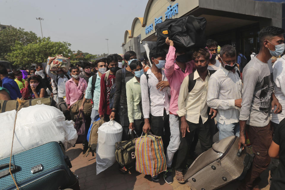 People wearing masks as a precaution against the coronavirus stand in queues to board trains at Lokmanya Tilak Terminus in Mumbai, India, Wednesday, April 14, 2021. India has been overwhelmed by hundreds of thousands of new coronavirus cases daily, bringing pain, fear and agony to many lives as lockdowns have been placed in Delhi and other cities around the country. (AP Photo/Rafiq Maqbool)