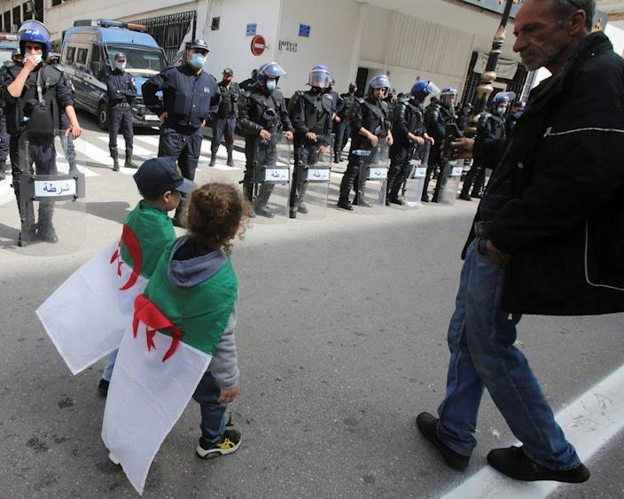 Children wearing Algeria's national flag walk past as police officers stand guard during a protest.