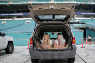Amanda Scherner, left, and Rachel Anhalt sit in their vehicle to watch a movie as part of the Outdoor Theater program offered by the Miami Dolphins at the Hard Rock Stadium amid the new coronavirus pandemic, Thursday, June 18, 2020, in Miami Gardens, Fla. The outdoor theater program offers a safe way for residents to safely get out of their homes and remain socially distant. (AP Photo/Lynne Sladky)