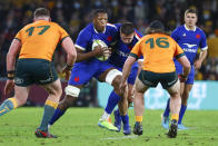 France's Cameron Woki runs at Australia's Lachlan Lonergan, right, and Australia's Angus Bell, left, during the rugby international between France and Australia at Suncorp Stadium in Brisbane, Australia, Wednesday, July 7, 2021. (AP Photo/Tertius Pickard)