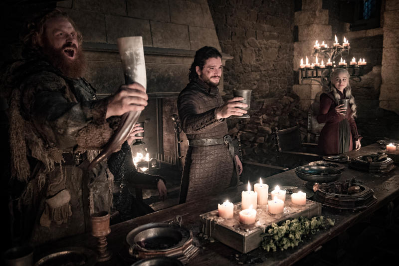 "This image released by HBO shows Kristofer Hivju, from left, Kit Harington and Emilia Clarke in a scene from ""Game of Thrones."" fans got a taste of the modern world when eagle-eyed viewers spotted a takeout coffee cup on the table during a celebration in which the actors drank from goblets and horns. The characters Daenerys and Jon did not react to the out of place cup in Sunday's episode. Many viewers complained the show should have caught the gaffe, which turned into an enduring meme on Monday.(Helen Sloan/HBO via AP)"