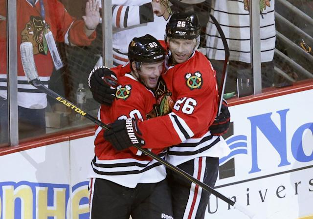 Chicago Blackhawks left wing Brandon Saad (20) and center Michal Handzus celebrate Saad's goal during the third period of an NHL hockey game against the Washington Capitals on Tuesday, Oct. 1, 2013, in Chicago. The Blackhawks won 6-4. (AP Photo/Charles Rex Arbogast)