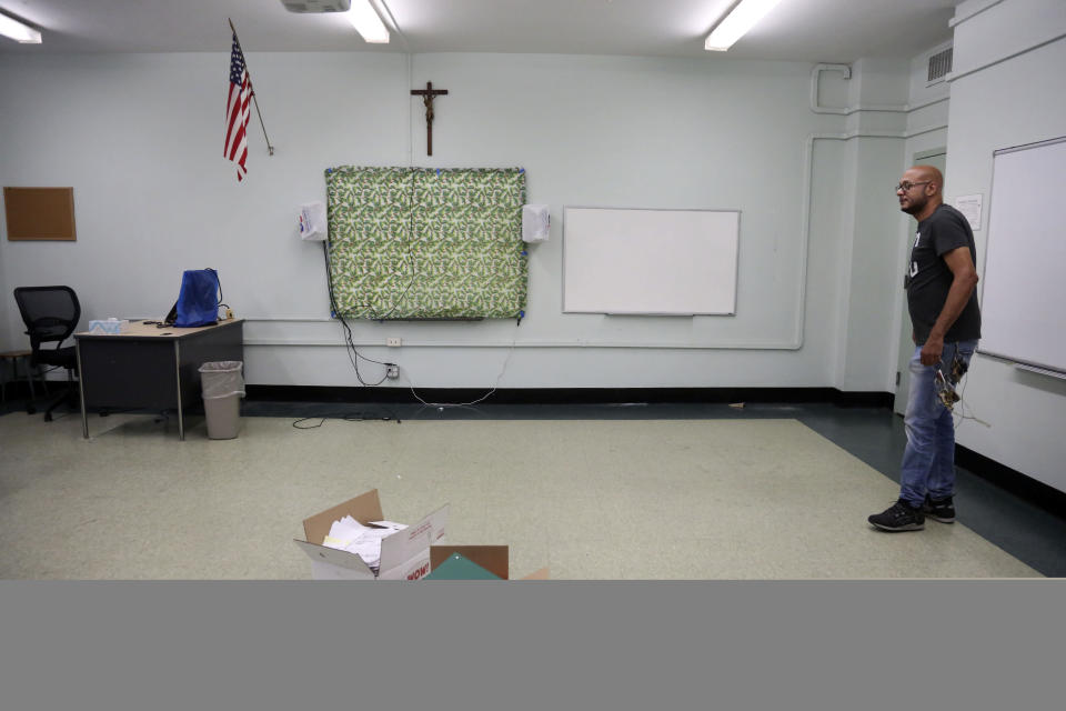 Facilities manager Charles Fabian stands in an empty classroom at Queen of the Rosary Catholic Academy in Brooklyn borough of New York, Thursday, Aug. 6, 2020. In July the Archdiocese of Brooklyn and Queens announced that six Catholic schools in the two boroughs will close permanently at the end of August due to debt and low enrollment aggravated by the coronavirus pandemic. (AP Photo/Jessie Wardarski)