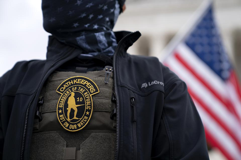 A demonstrator wears an OathKeepers anti-government organization badge on a protective vest during a protest outside the Supreme Court in Washington, D.C., U.S., on Tuesday, Jan. 5, 2021. (Stefani Reynolds/Bloomberg via Getty Images)