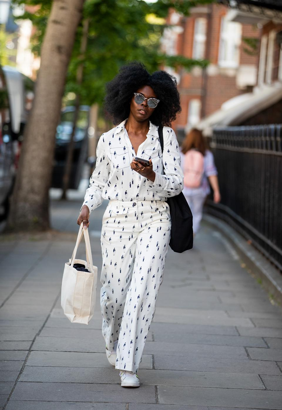 Deborah Ababio is seen wearing white button down shirt and printed trousers. [Photo: Getty Images]