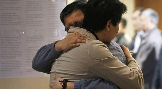 Two family members react to the news that potential debris of the missing MH370 flight was spotted off the coast of Western Australia. Photo: Reuters.