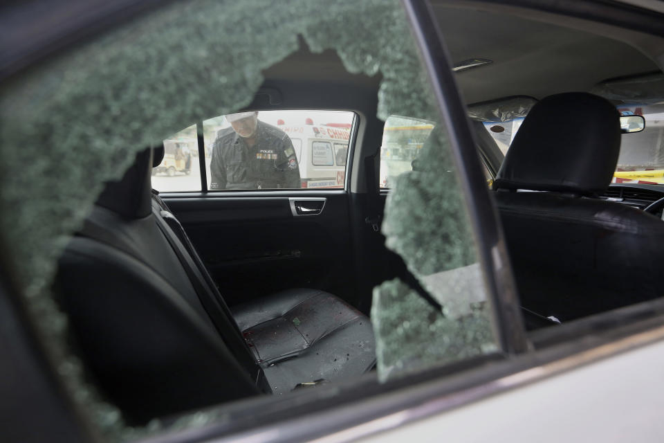 A police officer examines a damaged car at the site of a firing incident, in Karachi, Pakistan, Wednesday, July 28, 2021. Gunmen riding on a motorcycle fired into the car carrying two Chinese factory workers in Pakistan's port city of Karachi on Wednesday, wounding one of them before fleeing the scene, a rescue official and police said. (AP Photo/Fareed Khan)