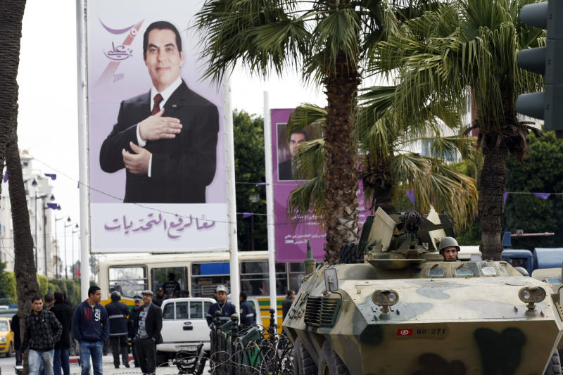 A armored vehicle guards a street in Tunis next to a photo of Tunisia's President Zine El Abidine Ben Ali, during a demonstration, Friday, Jan. 14, 2011. Thousands of angry demonstrators marched through Tunisia's capital Friday, demanding the resignation of the country's autocratic leader a day after he appeared on TV to try to stop deadly riots that have swept the North African nation. (AP Photo/Christophe Ena)