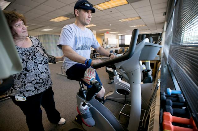 In this Thursday, April 3, 2014 photo, Boston Marathon bombing survivor Marc Fucarile, of Reading, Mass., right, is helped by physical therapy assistant Joy Ross, with rehabilitation exercises on a stationary bike at Spaulding Outpatient Center in Peabody, Mass. Fucarile lost his right leg in an explosion near the finish line of the 2013 race. (AP Photo/Steven Senne)