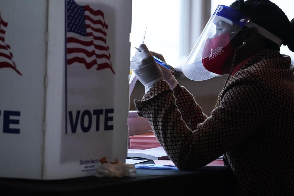 A poll worker talks to a voter before they vote on a paper ballot on Election Day in Atlanta on Tuesday, Nov. 3, 2020. (AP Photo/Brynn Anderson)