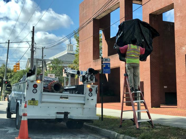 In this Oct. 28, 2019, photo, a worker with the North Carolina Department of Transportation covers the 1898 Wilmington coup highway historic marker that will be unveiled at a ceremony, in Wilmington, N.C. The marker commemorates the violent overthrow by white Democrats of the fusion government of legitimately elected blacks and white Republicans in Wilmington. The Democrats burned and killed their way to power in what's viewed as a flashpoint for the Jim Crow era of segregation and the only successful coup d'etat in American history. (Hunter Ingram/The Star-News via AP)
