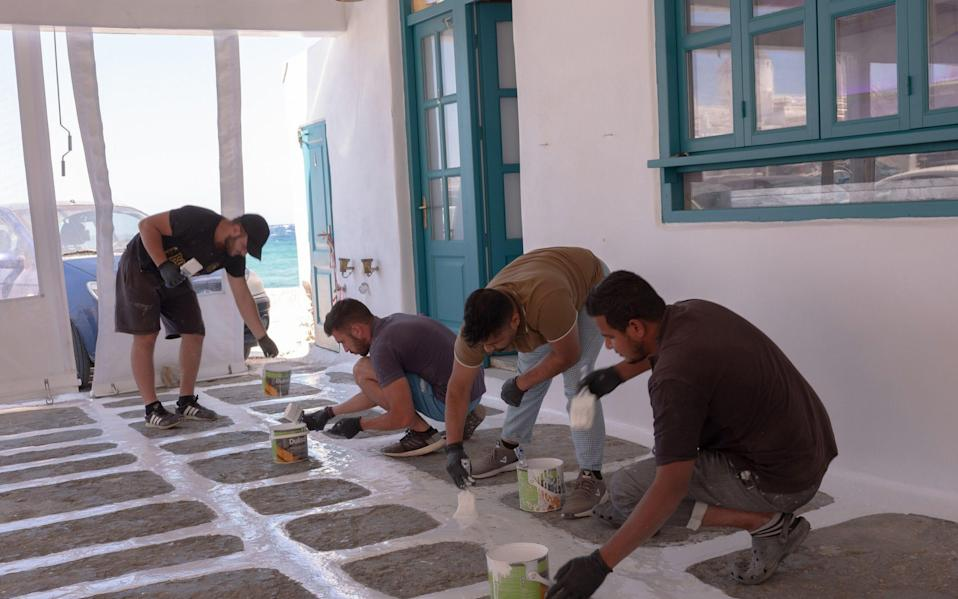 Workers paint a terrace floor in preparation for the reopening of bars and restaurants in the old town - Getty