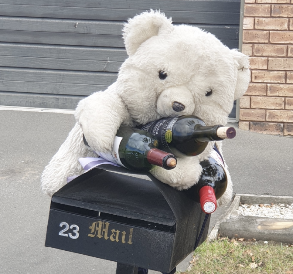 A stuffed bear is pictured on top of a mail box with empty wine bottles.
