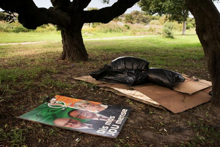 Politics and poverty: A campaign poster lies alongside the bedding of a homeless person in a Cape Town park ahead of the country's elections in May (AFP Photo/RODGER BOSCH)