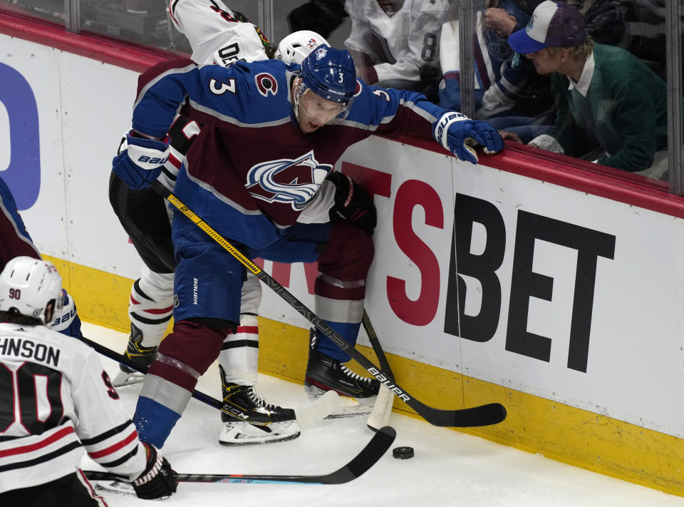 Colorado Avalanche defenseman Jack Johnson, front, fights for control of the puck with Chicago Blackhawks left wing Alex DeBrincat in the first period of an NHL hockey game Wednesday, Oct. 13, 2021, in Denver. (AP Photo/David Zalubowski)