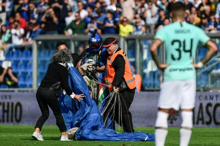 Security staff evacuate a parachutist who landed on the pitch at Sassuolo's Mapei Stadium during a game against Inter Milan