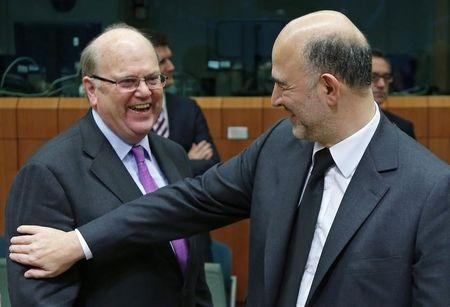 Irish Finance Minister Noonan talks to European Commissioner for economics, taxation and customs Moscovici during an Euro zone finance ministers meeting in Brussels