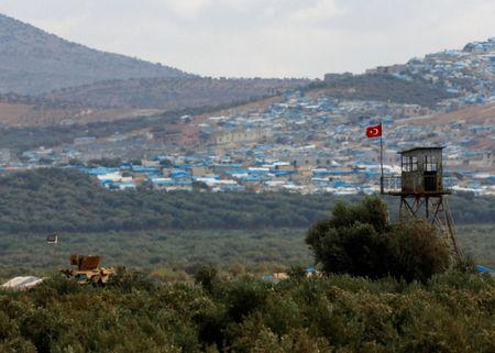 Turkish military armoured vehicle guards on the border line located opposite the Syrian town of Atimah