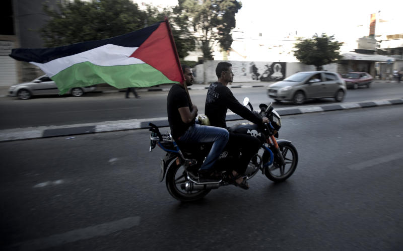 Palestinians carry the national flag as they ride through the streets of Gaza to celebrate the agreement to form a unity government on April 23, 2014