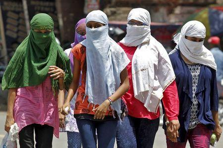 Girls, with faces covered to protect themselves from sun stroke, walk along a road on a hot summer day in Allahabad, India, May 29, 2015. REUTERS/Jitendra Prakash