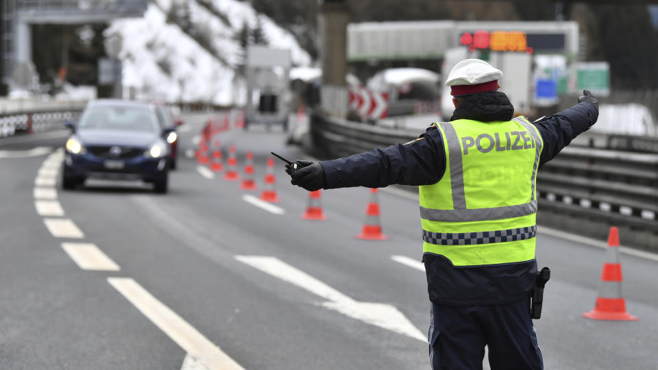 A policeman selects a car coming from Italy at the autobahn near Gries am Brenner on Tuesday, March 10, 2020. Austria authorities started on random checks of arriving vehicles at the border crossings with Italy in reaction to the outbreak of the new coronavirus in Europe, particularly in Italy. As part of the move, officials measure the temperatures of some passengers in cars, trucks and buses. For most people, the new coronavirus causes only mild or moderate symptoms, such as fever and cough. For some, especially older adults and people with existing health problems, it can cause more severe illness, including pneumonia. (AP Photo/Kerstin Joensson )